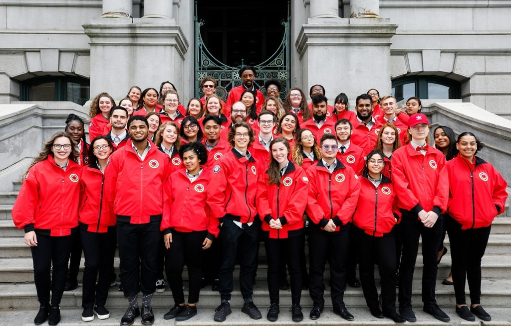 The City Year Providence corps stands on steps outside a stone building
